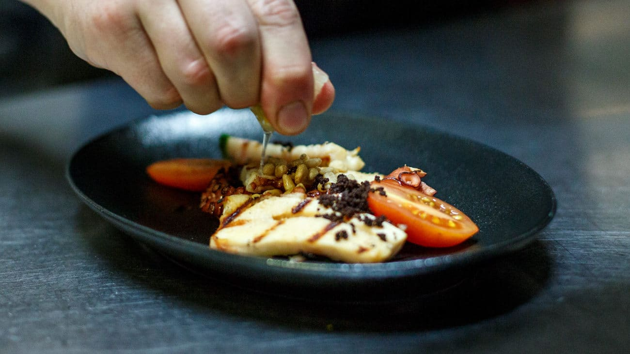 Grilled octopus, basil, olive powder, tomatoes, pine nuts